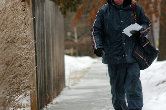 Gary Golinski, a Saratoga Springs postman, braves both snow and pouring rain as he delivers mail Friday in the city.