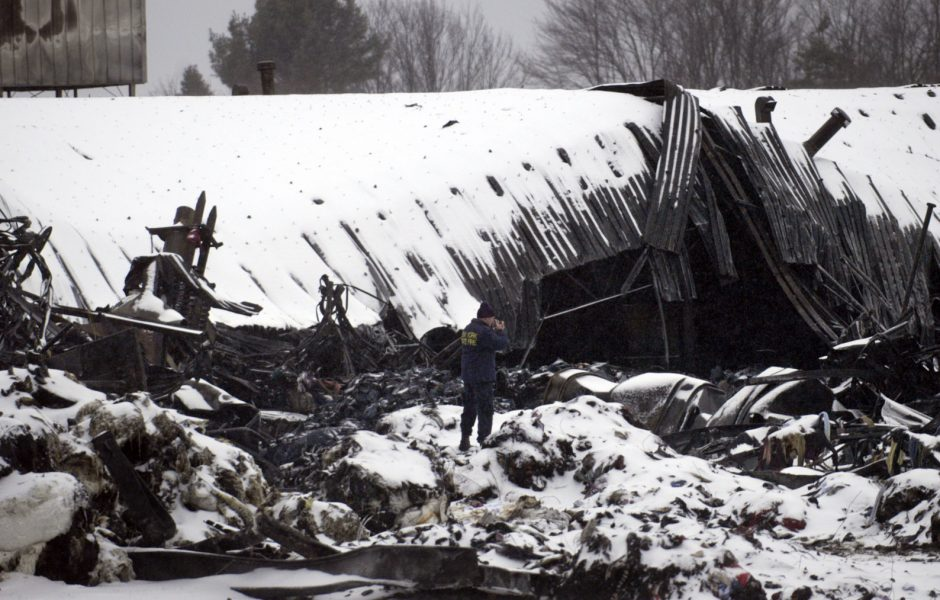 New York State Fire Investigator John Fairclough, center, stands upon ice-covered remains while photographing the scene at Fiber Conversion in Broadalbin on Friday. The factory suffered damage after a large fire on Thursday.