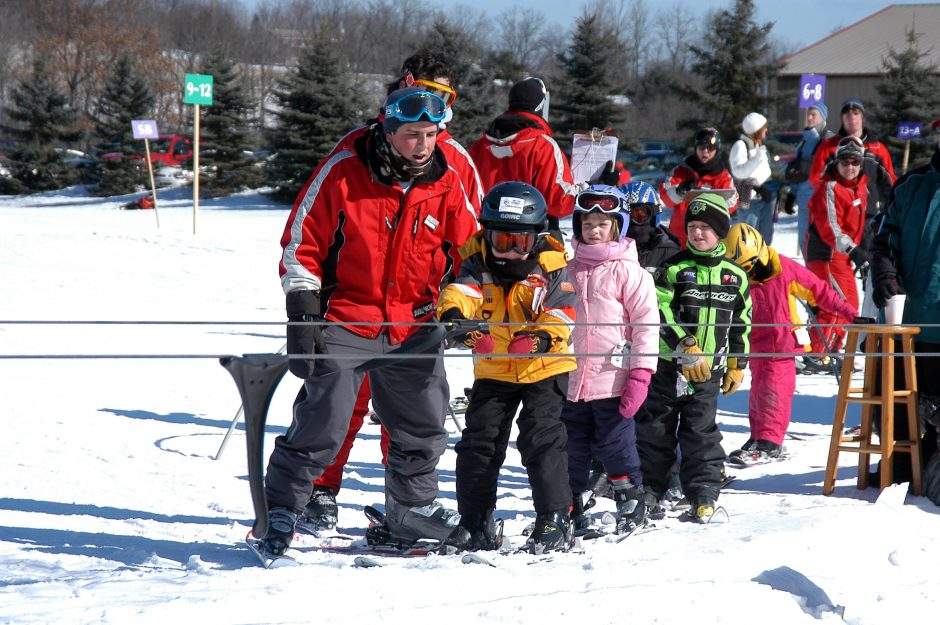 Enzo Mastroianni, a Schenectady Ski School instructor, assists young skiers riding the handle tow at Maple Ski Ridge in Rotterdam.