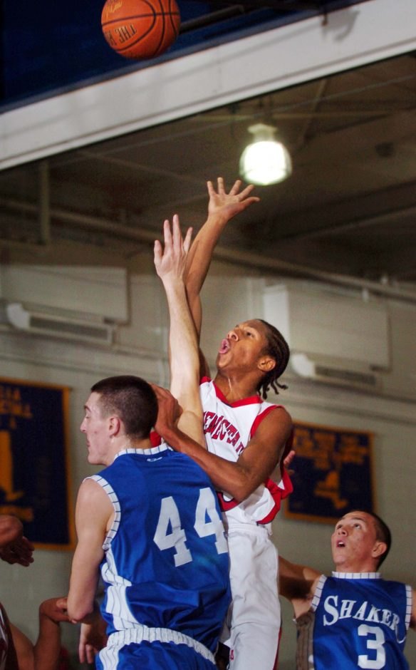 Schenectady's Tajric Boggs, center, goes up for a shot against Shaker's Ryan Sullivan, left, and John Weinheimer, right, during Wednesday's sectional basketball game at Schenectady high school.