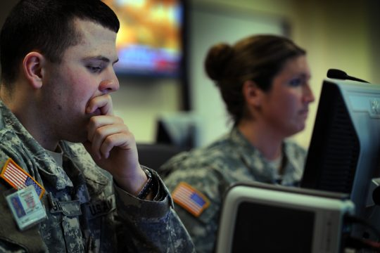 Lt. Sean Gill, left, and Sgt. Amy Cerrone work at computers in the new National Guard command center on Thursday.