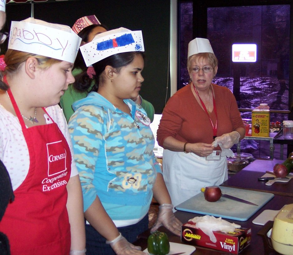 Cornell Cooperative Extension employee Eileen Lang, at right, helps students Gabby Chessier, left,  and Marilyn Rodriguez and other students learn how to prepare a healthy meal.