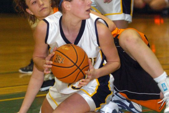 Recovering a fourth period rebound, Averill Park's Katie Duma looks to pass to a teammate as Mohonasen's Nicole Adach watches from the floor.