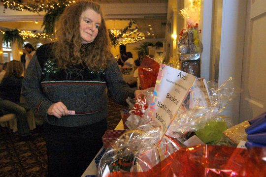 Jean Tecler of Edinburg looks auction items Sunday during a fundraiser for Debbie Lees and her children at the Glen Sanders Mansion in Scotia. Tecler attended the event in support of Lees, who is her co-worker.