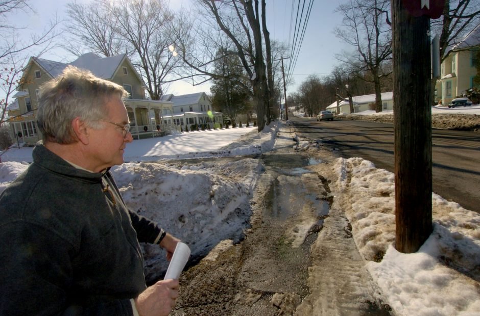Sharon Springs Central School neighbor Michael Whaling looks at snowmobile tracks along Chestnut Street near the school on Monday.