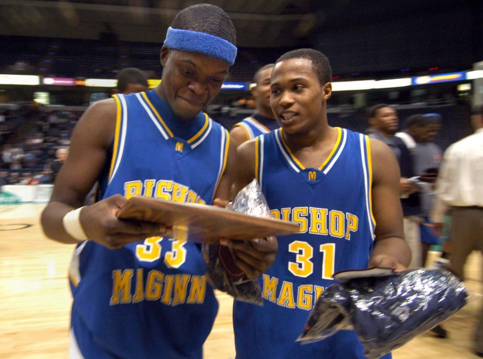 Bishop Maginn's Bunduka Kargbo, left, and Terron Victoria, right, get a closer look at the Class AA award after beating CBA Monday evening at the Times Union Center in Albany.