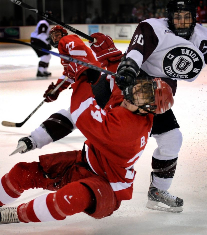 Brendan Nash of Cornell, left, loses his helmet after being clothes-lined by Matt Cook of Union Friday.