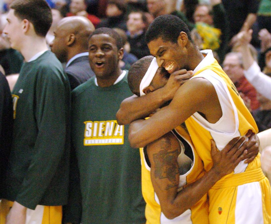 Siena's Edwin Ubiles, right, envelopes Tay Fisher as the Saints wrap up the last few seconds of their MAAC championship game Monday against Rider at the Times Union Center in Albany to win the division.