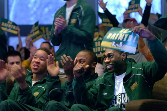 Siena men's basketball players Erik Harris, left, Kenny Hasbrouck, center, and Taye Fisher applaud after the team learned its NCAA tournament opponent on Sunday. Siena, the Midwest Region's 13th seed, will meet fourth-s