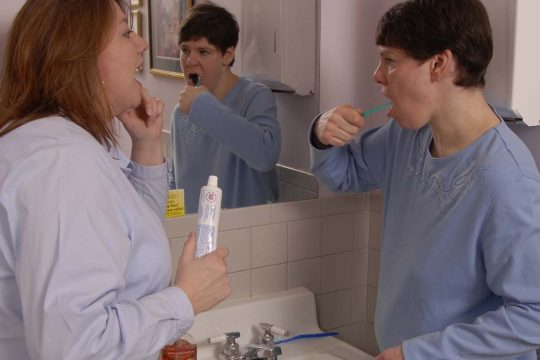 A staffer from the Office of Mental Retardation and Developmental Disabilities, left, instructs a person with a disability on proper dental care.