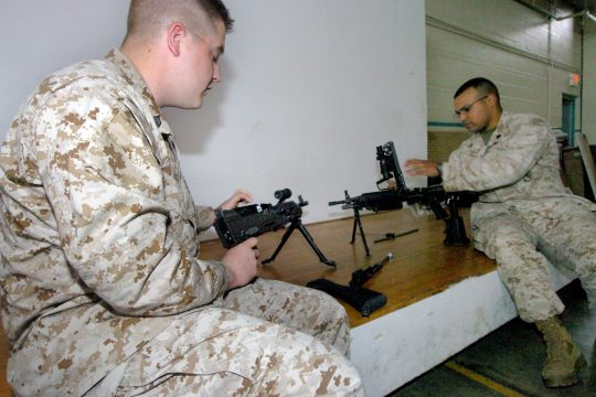 Marine reservist Sgt. Raymond Elwell, left, and active duty Marine Sgt. Dennis Pichardo, both members of the 2nd Battallion, 25th Marine Regiment, Fox Company, inspect and adjust new weapons Tuesday at the Marine armory on Washington Avenue in Albany.
