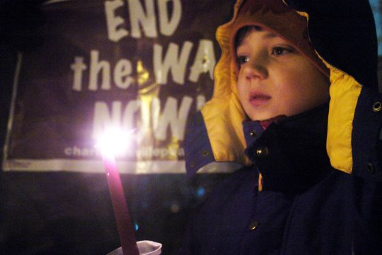 Gabriel Baskin, 7, of Ballston Spa, participates in a Wednesday night vigil marking the fifth anniversary of the War in Iraq, held at Broadway in Saratoga Springs. Baskin attended the vigil with his parents.