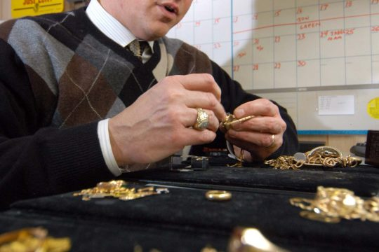 Jon Sosnowski, co-owner of Mayfair Jewelers in Glenville, looks through a pile of gold jewelry on Thursday.