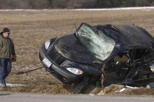 A tow truck driver waits for a PT Cruiser to land on its wheels as it is righted following a crash involving a Montgomery County Department of Public Works truck on Stoners Trail Road in Mohawk on Friday morning.