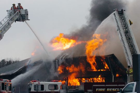 Flames break through the roof late Thursday afternoon as fire destroys the House of Furniture on Route 30 in Perth.