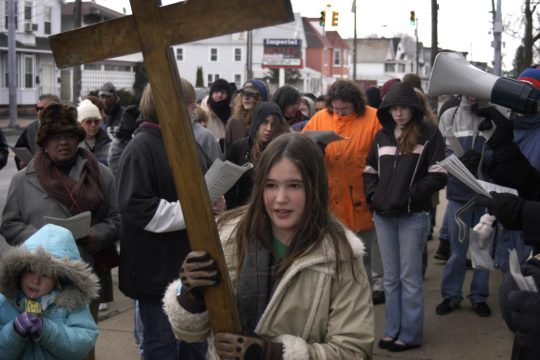 Eleven-year-old Moriah Jones, daughter of the Rev. Brad Jones of Christ Church Episcopal, carries the cross west on State Street in Schenectady to the next station during the Stations of the Cross Good Friday procession.