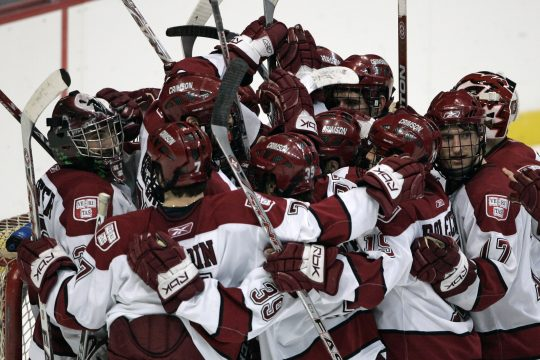 Harvard University goalie Kyle Richter, left, is mobbed by teammates after the Crimson defeated Cornell University, 3-1, in their ECAC Hockey semifinal game Friday night at the Times Union Center.  (AP Photo/Mike Groll)
