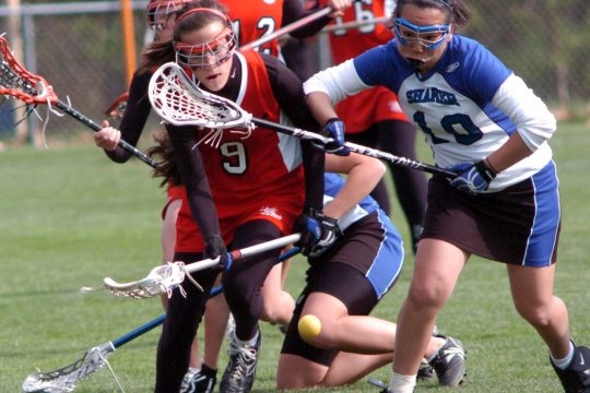 ------Kristen Cagino of Guilerland, left, and S. Kim of Shaker chase a loose ball in first half girls' lacrosse action Wednesday at Shaker.