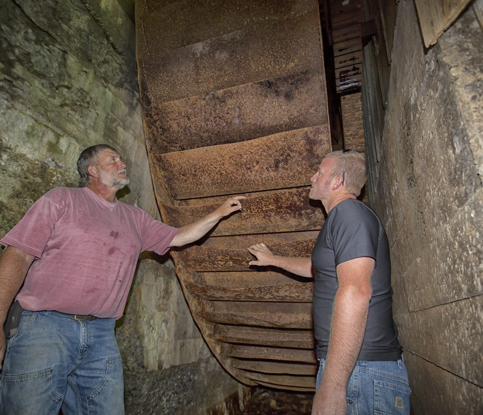 James Swartout, left and his son, Chris Swartout, check out the metal buckets on the metal water wheel beneath the Bunn-Tillapaugh Feed Mill. They, along with two other members of the Richmondville Historical Society, restored the operation of the wheel,