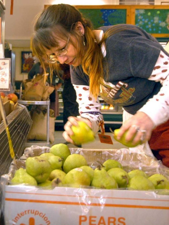 Stacie Halloran, an employee of the Honest Weight Food Co-op in Albany, stocks organic and fair-trade pears.