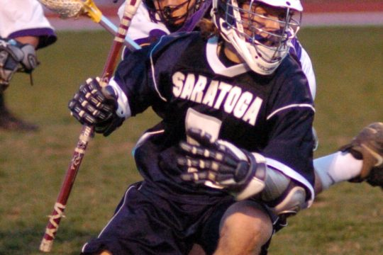 Saratoga Springs' Nico Cortese guards the ball as he advances it through the Ballston Spa defense in the first half of a high school varsity lacrosse match Tuesday night.