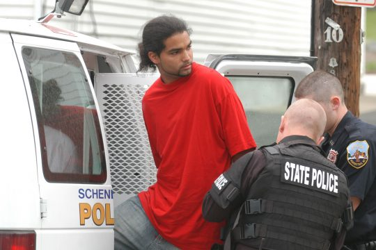 State and Schenectady police move Hector L. Gomez into an awaiting police holding van along the 1600 block of Foster Avenue on Thursday.