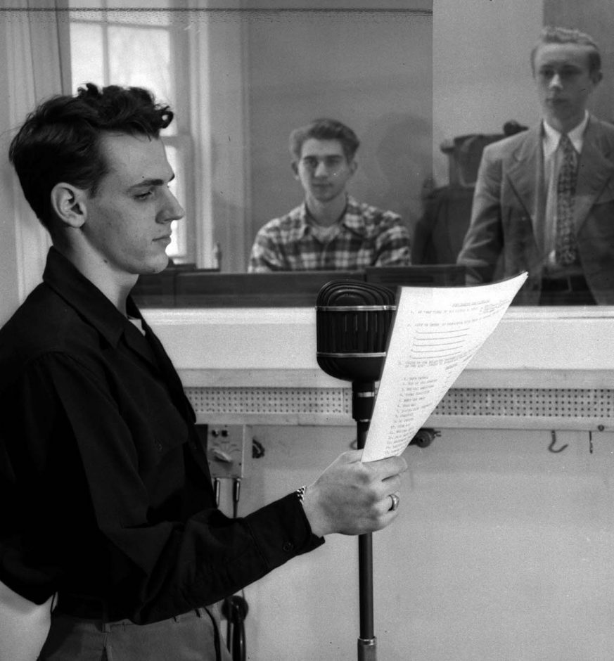Ashton W. Hart prepares his voice for a news broadcast at Union College in 1948. Dave Zierk sits in the control room, ready to transmit the signal to campus listeners.