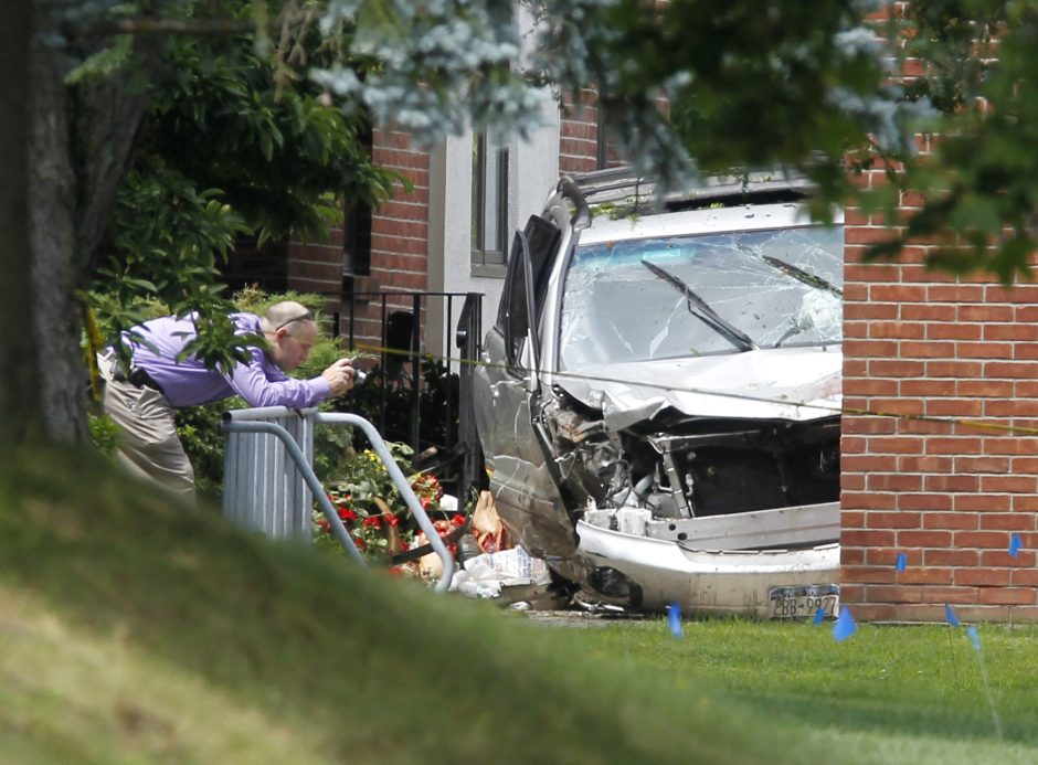 A law enforcement official photographs a vehicle in front of St. Matthew's Roman Catholic Church in Voorheesville, where three pedestrians were killed in August 2011.