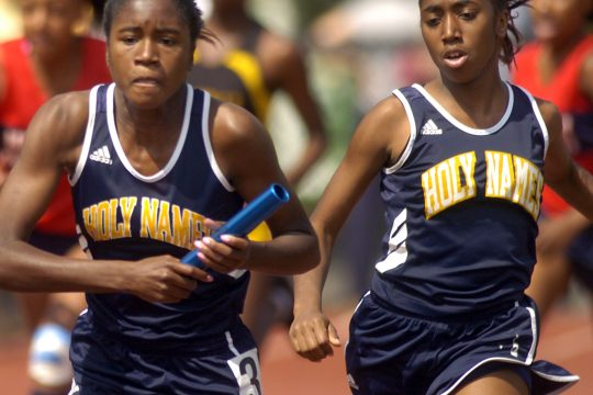 Holy Names' Klarissa Ricks, left, receives the baton from teammate Sherez Mohamed during the Girls 400 meter relay at the 68th annual Eddy Track Meet held at Union College Saturday. Holy Names place first in the event.