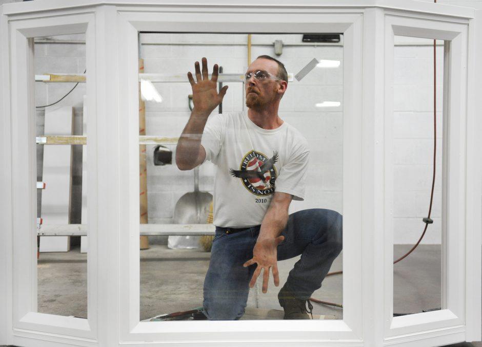 Matthew Rackmyer of Kasson & Keller Inc., a vinyl window manufacturer in Fonda, works on a bay window assemby.