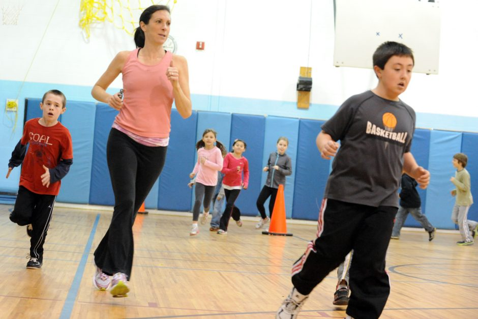 Teacher Dana Bush warms up with students in grades 3 through 5 at Geyser Road Elementary School.