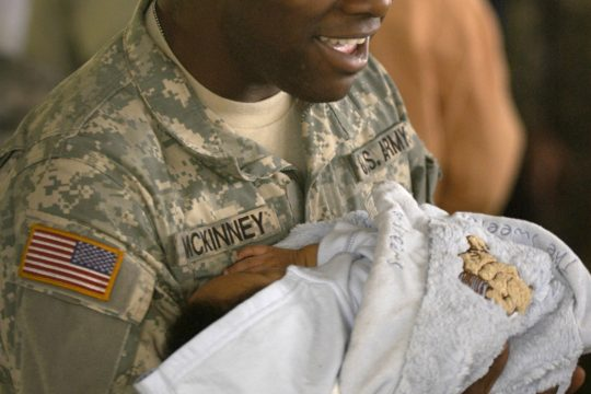 """Turel McKinney of Albany dances to """"New York, New York"""" with his 2-month-old nephew, Isaiah Hermitt, at the deployment farewell ceremony held Sunday at the Saratoga County Fairgrounds. McKinney and the other members of his battalion will deploy"""