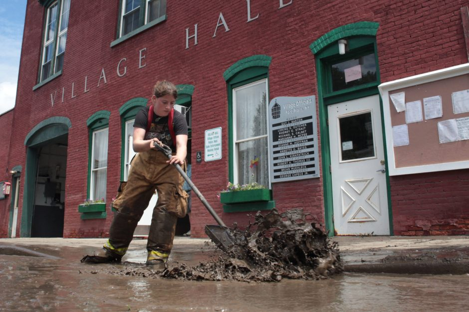 Michaela Schuyler, 19, a volunteer with the Fort Plain Fire Department, shovels muddy water in front of the Village Hall following flooding in Fort Plain on Friday, June 28, 2013.