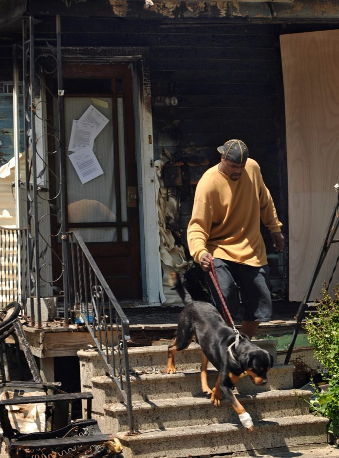 Rashawn Harris of 1110 Second Ave. in Schenectady leads a dog from his home after a fire Tuesday morning.