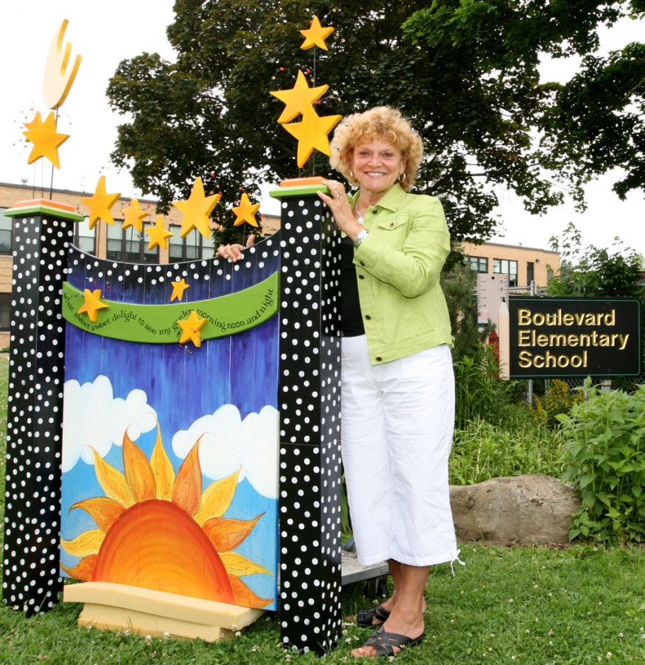 """Cindy Sheeler poses with her garden gate, """"What Sweet Delight,"""" at the Boulevard Elementary School, where she teaches, in Gloversville Wednesday morning.  Her garden gate was selected to be displayed as part of the """"In Full Bloom: Artists D"""