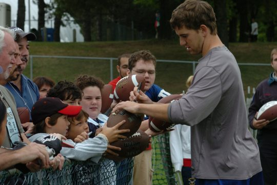 New York Giants quarterback Eli Manning, Super Bowl MVP, signs autographs for fans during training camp last summer at the University at Albany. (University at Albany photo) l