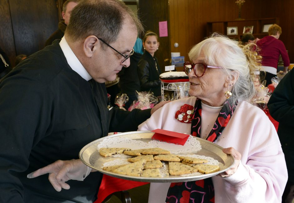The Rev. Michael Neufeld, left, talks with Nanci Wilson while restocking baked goods at the sixth annual Chocolate Fest at St. Andrews Church in Scotia on Saturday.