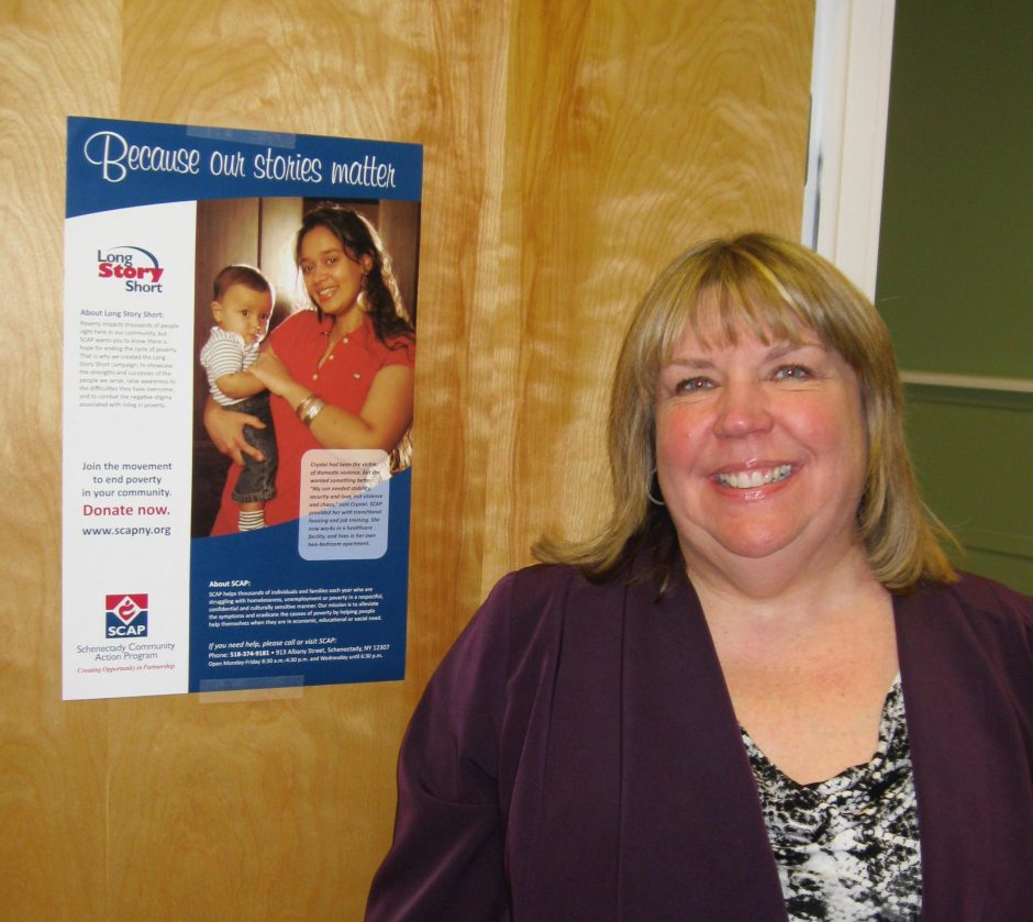Deb Schimpf, executive director of the Schenectady Community Action Program, stands next to one of the group's Long Story Short posters.