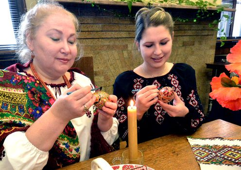 Olya Szyjka, left, and Anastasia Kostyk, right, demonstrate Ukraine pysanky, the art of painting on eggs, at the Amsterdam Free Library on Monday afternoon.