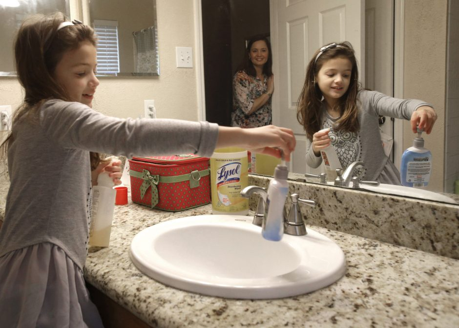 Lily Cherry, 8, cleans her bathroom as her mother, Andrea, supervises at their home in Kingwood, Texas.