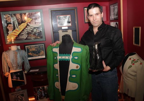 "Wayne Newcomb poses for a picture with his ""Wizard of Oz"" costumes, part of his personal golden era movie memorabilia collection."