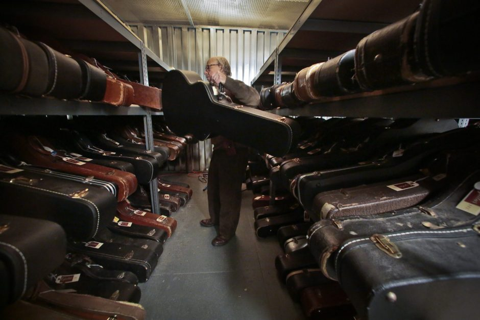 Arlan Ettinger, president of Guernsey's, auctioneers, return an encased guitar to its warehouse shelve during a press preview, March 5 in New York. Guernsey's has warehoused a collection of 265 extremely rare guitars from a single individual, which goe...