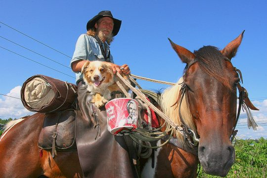 Mick Thompson sits astride his horse as he arrives in Amsterdam Tuesday evening. Thompson, his horse Hawkeye and dog Yogi are journeying across the country from Oregon to Maine.