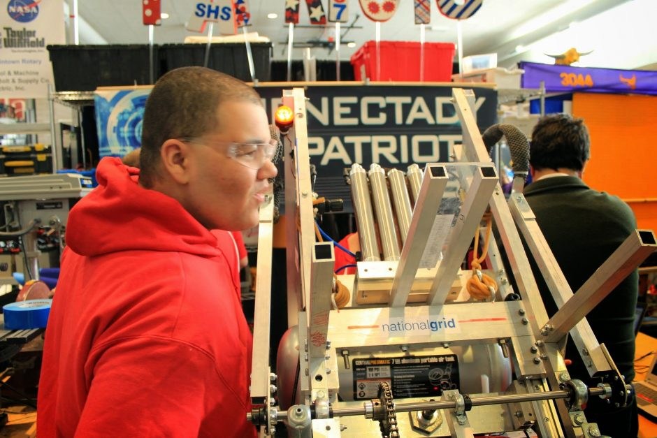 A member of the Schenectady High School team makes adjustments to their robot before competition.