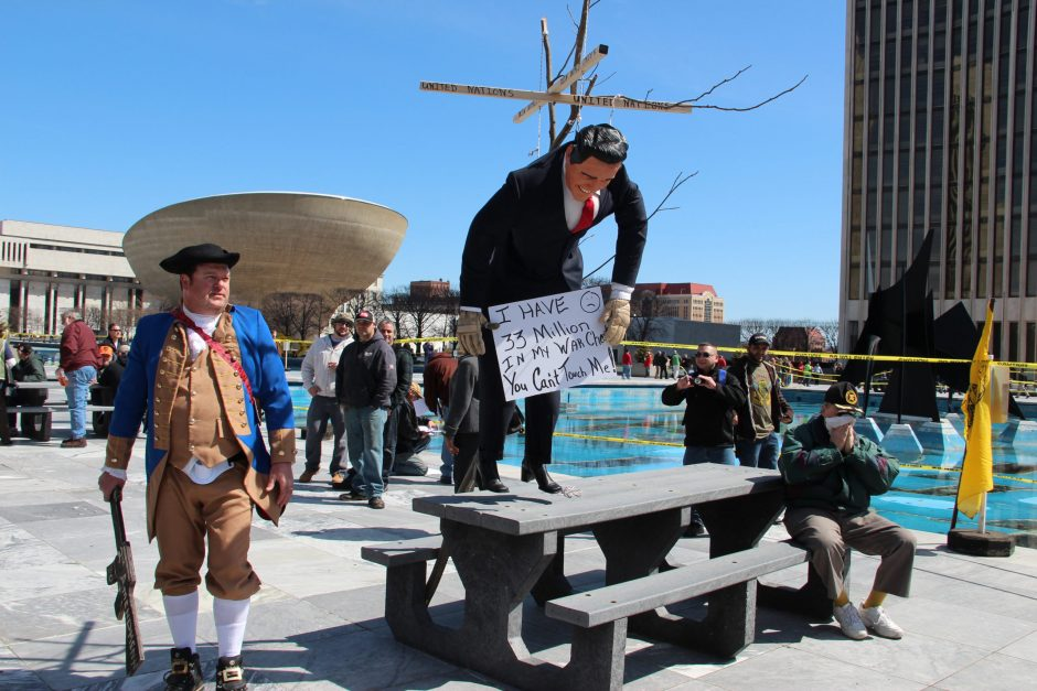 A veteran brought a life-size Gov. Andrew Cuomo doll, portrayed as a puppet hanging from strings. The sign read, 'I have $33 million in my war chest, you can't touch me!'