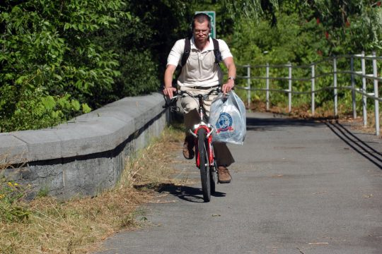 Jim Reed of Scotia passes over the bike path aqueduct bridge near Kiwanis Park in Rotterdam on Thursday as he makes his way west after a day of work.
