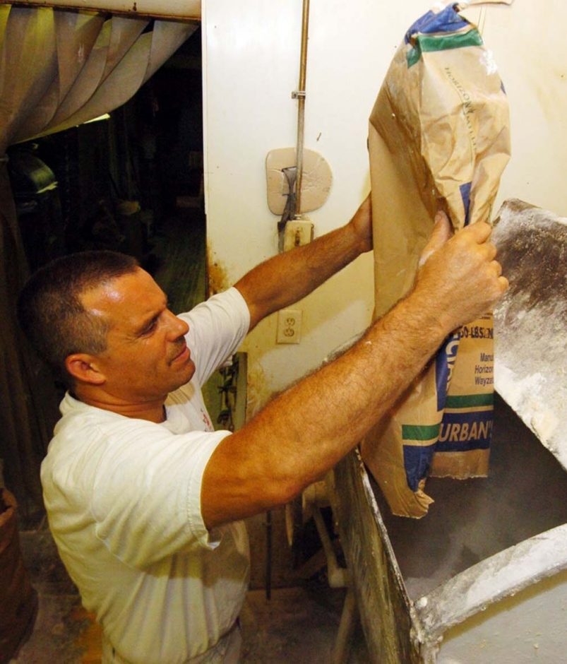 Working at a mixing machine he inherited from his grandfather, owner Tony Papa dumps a bag of flour as he makes bread dough at Perecca's Bakery in Schenectady. He says he is doing all he can to reduce energy costs, such as installing mor