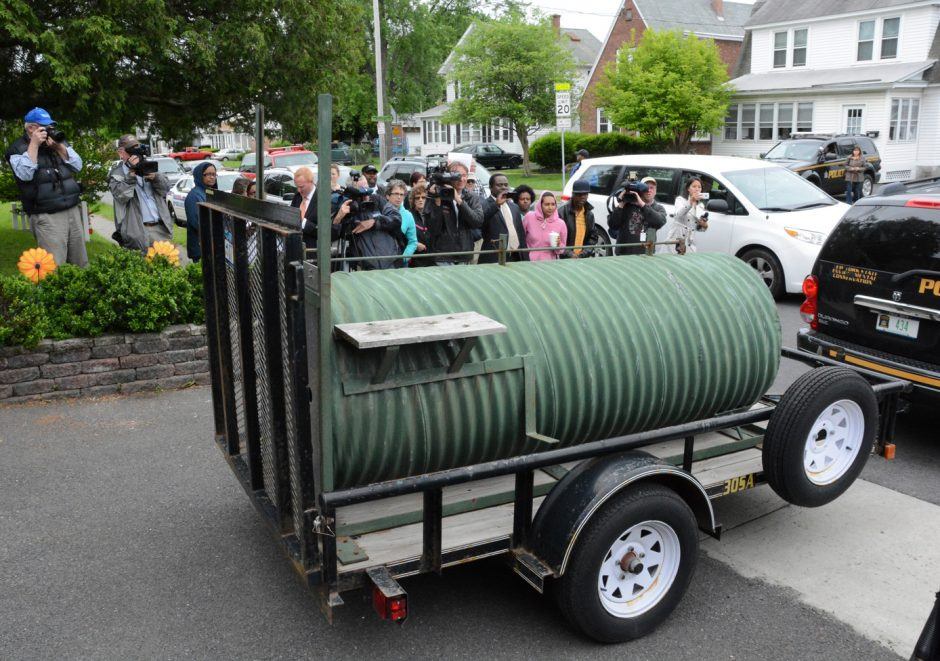 DEC officials move a black bear in an enclosed trailer from the rear of a home in Albany on Wednesday. The bear was in a tree for 24 hours before being tranquilized and falling to the ground.