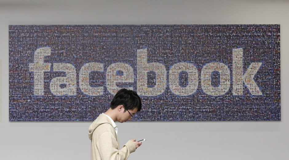 A man walks past a Facebook sign in an office on the Facebook campus in Menlo Park, Calif.