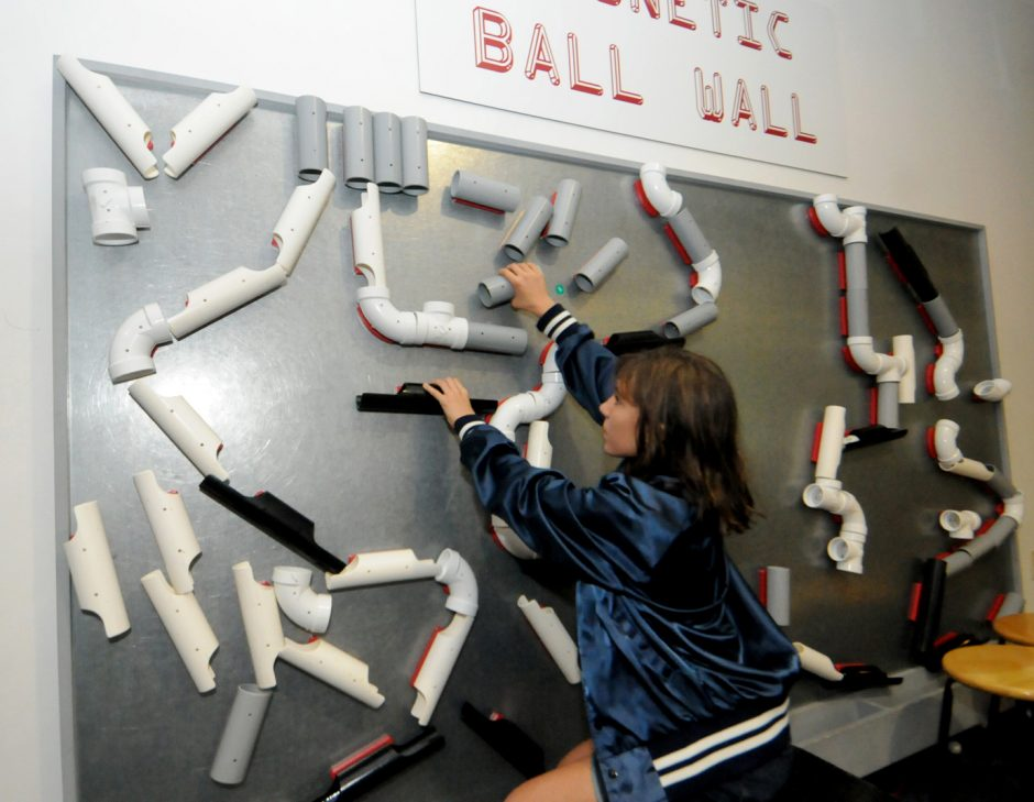 Maya Turcotte moves plastic piping around to make a design on the magnetic ball wall at The Childrens Museum of Science and Technology in the RPI Technology Park in Troy.
